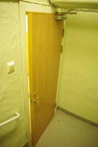 Foto som visar dörrstängare på en källardörr.