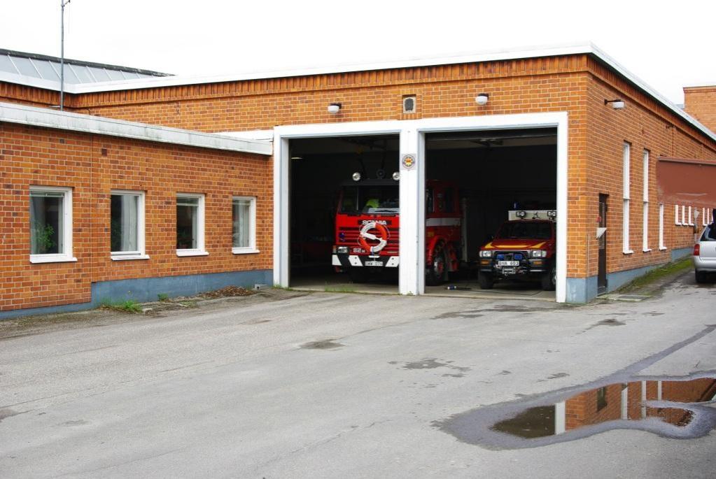 Foto på brandstationen i Högsjö, taget utifrån där fronten på två brandbilar syns.