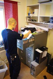 Foto av brandingenjör som bläddrar bland dokument i ett arkivskåp.