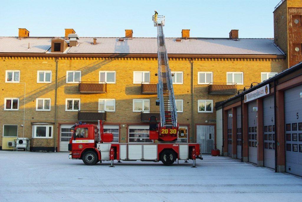 Foto på stegbil med stegen upphissad, taget utanför gamla brandstationen i Katrineholm.